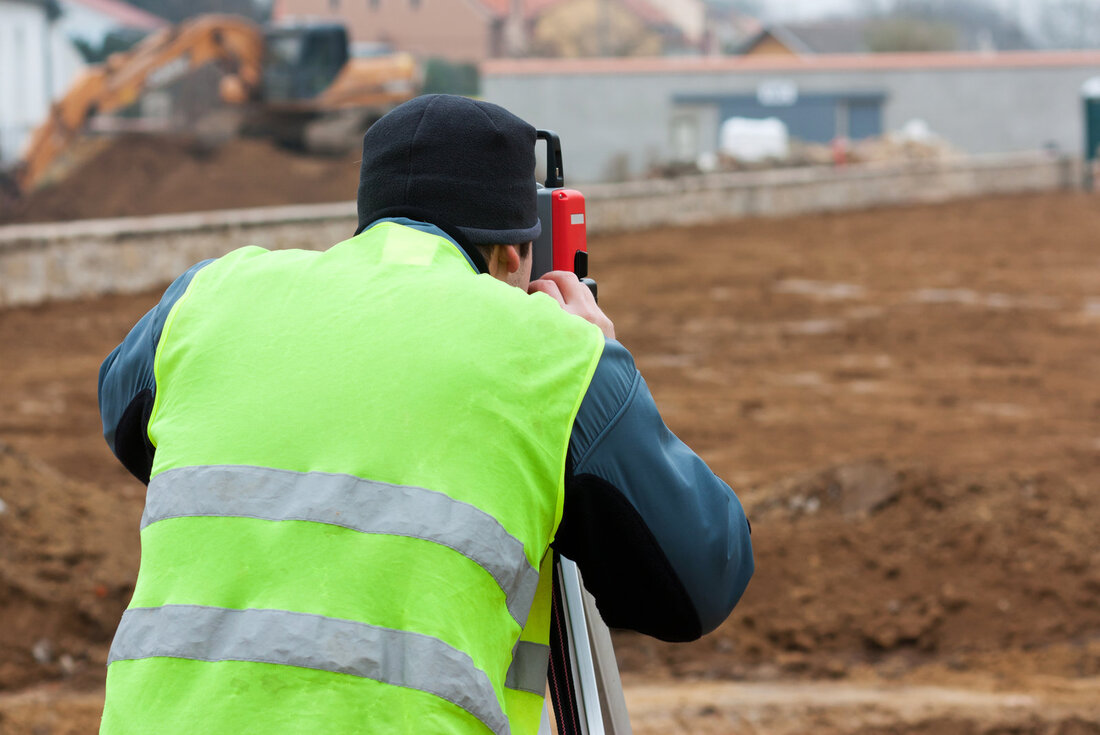 man at the construction site is using topographic survey